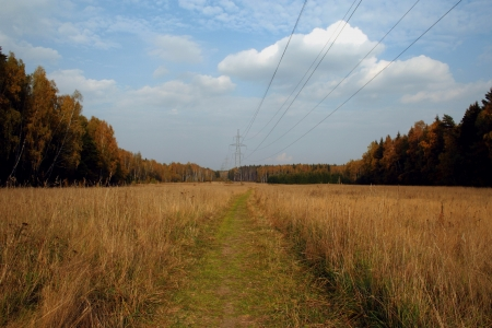 sun and clouds over rural road, power transmission line and the forest photo