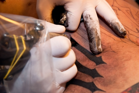 gun room: a tattoo artist imprinting his art with black ink on a stomach of a young guy Stock Photo