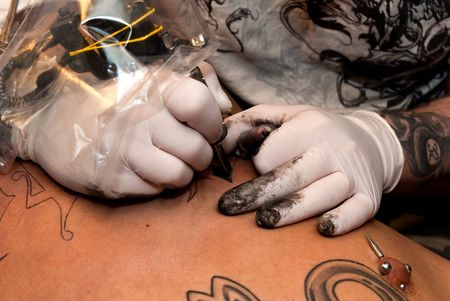 a tattoo artist imprinting his art with black ink on a stomach of a young guy photo