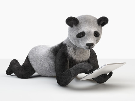 oso panda: panda acostado en el vientre que mira la tablilla. Foto de archivo