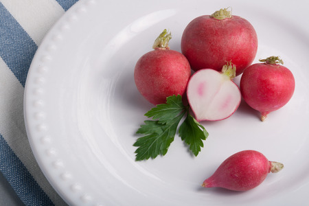 whote: Five radishes on a whote plate