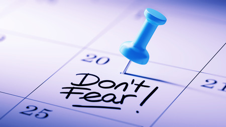 dont: Concept image of a Calendar with a blue push pin. Closeup shot of a thumbtack attached. The words Dont Fear written on a white notebook to remind you an important appointment.
