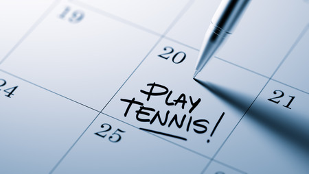 written date: Closeup of a personal agenda setting an important date written with pen. The words Play Tennis written on a white notebook to remind you an important appointment.