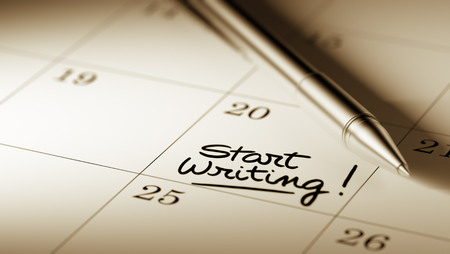written date: Closeup of a personal agenda setting an important date written with pen. The words Start Writing written on a white notebook to remind you an important appointment. Stock Photo