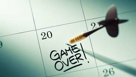 Conceptbeeld van een kalender met een gouden dartstok. De woorden Game over geschreven op een wit notitieboek om je een belangrijke afspraak te herinneren.