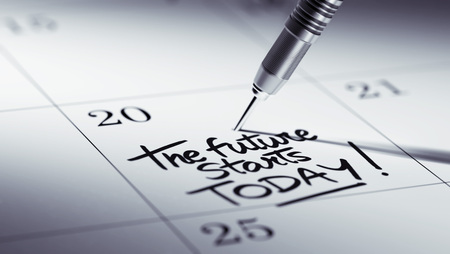 black empowerment: Concept image of a Calendar with a golden dart stick. The words The future starts today written on a white notebook to remind you an important appointment. Stock Photo