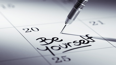 be yourself: Concept image of a Calendar with a golden dart stick. The words be yourself written on a white notebook to remind you an important appointment. Stock Photo