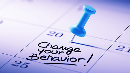 Concept image of a Calendar with a blue push pin. Closeup shot of a thumbtack attached. The words Change your behavior written on a white notebook to remind you an important appointment.