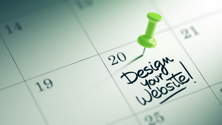website words: Concept image of a Calendar with a green push pin. Closeup shot of a thumbtack attached. The words Design your website written on a white notebook to remind you an important appointment. Stock Photo