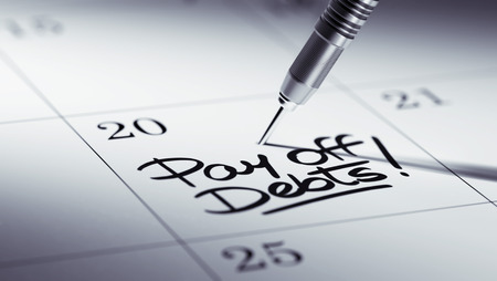 pay off: Concept image of a Calendar with a golden dart stick. The words Pay off debts written on a white notebook to remind you an important appointment. Stock Photo
