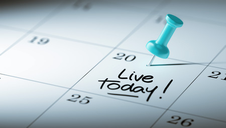 living moment: Concept image of a Calendar with a blue push pin. Closeup shot of a thumbtack attached. The words Live today written on a white notebook to remind you an important appointment.