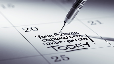 depends: Concept image of a Calendar with a golden dart stick. The words Your future depends on what you do today written on a white notebook to remind you an appointment.