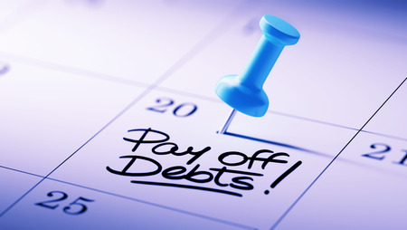 pay off: Concept image of a Calendar with a blue push pin. Closeup shot of a thumbtack attached. The words Pay off debts written on a white notebook to remind you an important appointment.