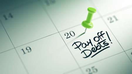 pay off: Concept image of a Calendar with a green push pin. Closeup shot of a thumbtack attached. The words Pay off debts written on a white notebook to remind you an important appointment. Stock Photo