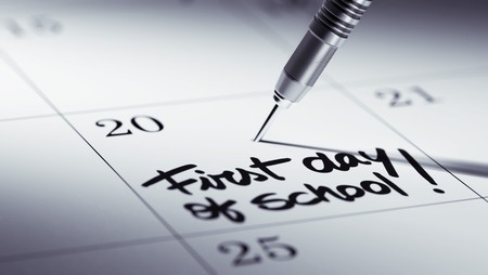 Concept image of a Calendar with a golden dart stick. The words First day of school written on a white notebook to remind you an important appointment. Stock Photo