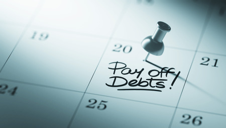 pay off: Concept image of a Calendar with a push pin. Closeup shot of a thumbtack attached. The words Pay off debts written on a white notebook to remind you an important appointment. Stock Photo
