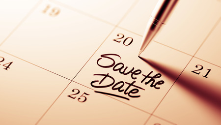 Closeup of a personal agenda setting an important date written with pen. The words Save the date written on a white notebook to remind you an important appointment.