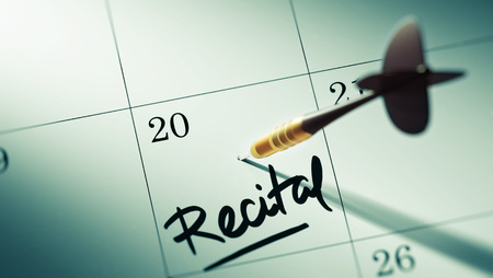 recital: Concept image of a Calendar with a golden dart stick. The words Recital written on a white notebook to remind you an important appointment. Stock Photo
