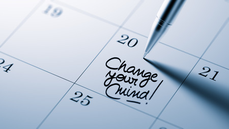 Closeup of a personal agenda setting an important date written with pen. The words Change your Mind written on a white notebook to remind you an important appointment. Stock Photo