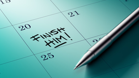 liquidate: Closeup of a personal agenda setting an important date written with pen. The words Finish Him written on a white notebook to remind you an important appointment.
