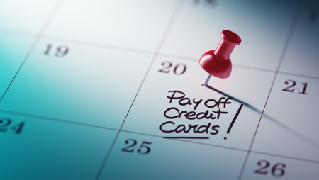pay off: Concept image of a Calendar with a red push pin. Closeup shot of a thumbtack attached. The words Pay off Credit cards written on a white notebook to remind you an important appointment.