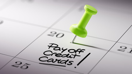 pay off: Concept image of a Calendar with a green push pin. Closeup shot of a thumbtack attached. The words Pay off Credit cards written on a white notebook to remind you an important appointment. Stock Photo