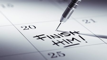 liquidate: Concept image of a Calendar with a golden dart stick. The words Finish Him written on a white notebook to remind you an important appointment.