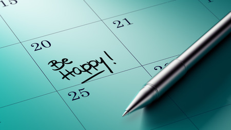 written date: Closeup of a personal agenda setting an important date written with pen. The words Be happy written on a white notebook to remind you an important appointment.