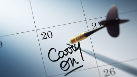 persist: Concept image of a Calendar with a golden dart stick. The words Carry on written on a white notebook to remind you an important appointment. Stock Photo