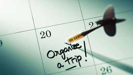 organize: Concept image of a Calendar with a golden dart stick. The words Organize a Trip written on a white notebook to remind you an important appointment.