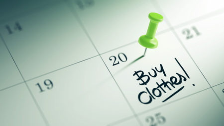 clothes organizer: Concept image of a Calendar with a green push pin. Closeup shot of a thumbtack attached. The words Buy Clothes written on a white notebook to remind you an important appointment.