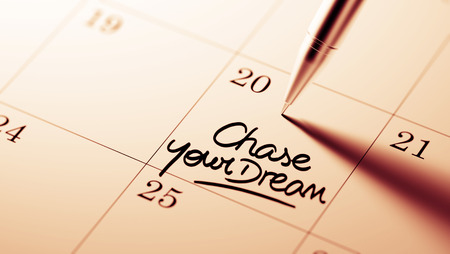 Closeup of a personal agenda setting an important date written with pen. The words Chase your dream written on a white notebook to remind you an important appointment.