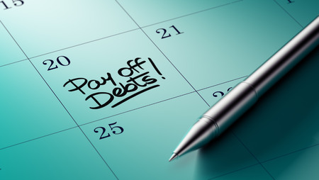 pay off: Closeup of a personal agenda setting an important date written with pen. The words Pay off debts written on a white notebook to remind you an important appointment.