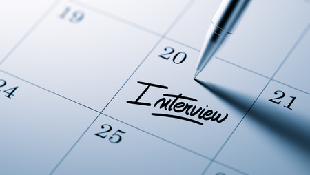 comunicacion oral: Primer plano de una fijaci�n de una fecha importante por escrito con la pluma agenda personal. La Entrevista palabras escritas en un cuaderno en blanco para que le recuerde una cita importante.