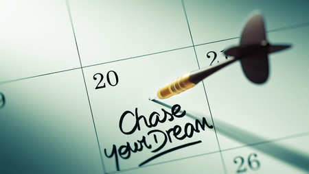 Concept image of a Calendar with a golden dart stick. The words Chase your dream written on a white notebook to remind you an important appointment. Stock Photo