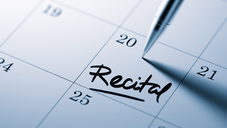 recital: Closeup of a personal agenda setting an important date written with pen. The words Recital written on a white notebook to remind you an important appointment.