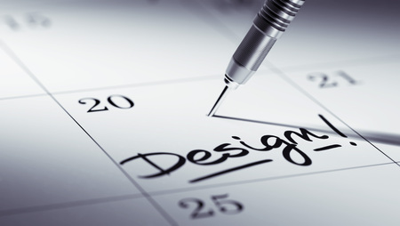 remind: Concept image of a Calendar with a golden dart stick. The words Design written on a white notebook to remind you an important appointment. Stock Photo
