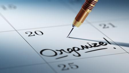 황금 다트 스틱 달력의 컨셉 이미지. Organize라는 단어는 중요한 약속을 상기시키기 위해 흰색 노트북에 쓰여 있습니다.