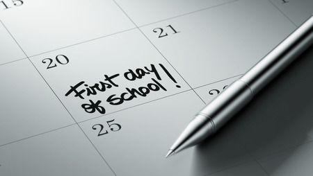 initiate: Closeup of a personal agenda setting an important date written with pen. The words First day of school written on a white notebook to remind you an important appointment. Stock Photo