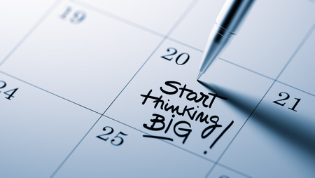 written date: Closeup of a personal agenda setting an important date written with pen. The words Start thinking BIG written on a white notebook to remind you an important appointment.