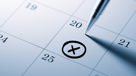 important date: Closeup of a personal agenda setting an important date written with pen. X mark written on a white notebook to remind you an important appointment.