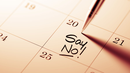 denying: Closeup of a personal agenda setting an important date written with pen. The words Say NO written on a white notebook to remind you an important appointment. Stock Photo