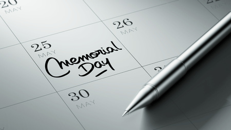 written date: Closeup of a personal agenda setting an important date written with pen. The words Memorial Day written on a white notebook to remind you an important appointment.