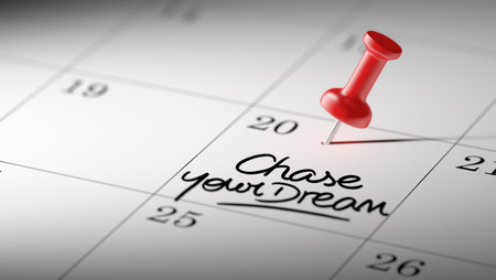 chase: Concept image of a Calendar with a red push pin. Closeup shot of a thumbtack attached. The words Chase your dream written on a white notebook to remind you an important appointment.