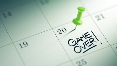 the game is over: Concept image of a Calendar with a green push pin. Closeup shot of a thumbtack attached. The words Game over written on a white notebook to remind you an important appointment. Stock Photo