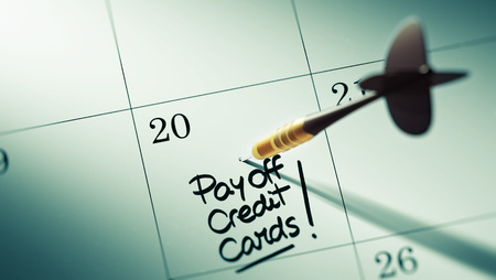 pay off: Concept image of a Calendar with a golden dart stick. The words Pay off Credit cards written on a white notebook to remind you an important appointment.