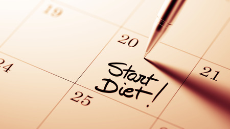 important date: Closeup of a personal agenda setting an important date written with pen. The words Start Diet written on a white notebook to remind you an important appointment. Stock Photo