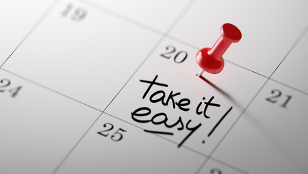 take it easy: Concept image of a Calendar with a red push pin. Closeup shot of a thumbtack attached. The words Take it easy written on a white notebook to remind you an important appointment.