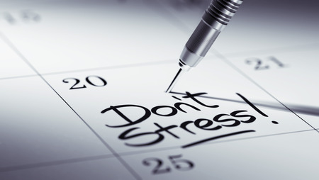 dont: Concept image of a Calendar with a golden dart stick. The words Dont Stress written on a white notebook to remind you an important appointment.