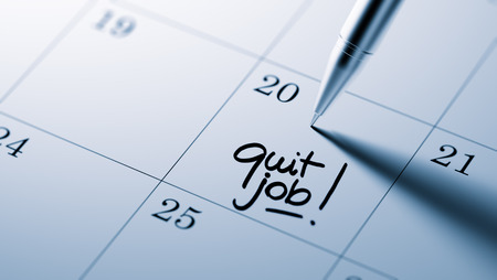 important date: Closeup of a personal agenda setting an important date written with pen. The words Quit job written on a white notebook to remind you an important appointment. Stock Photo